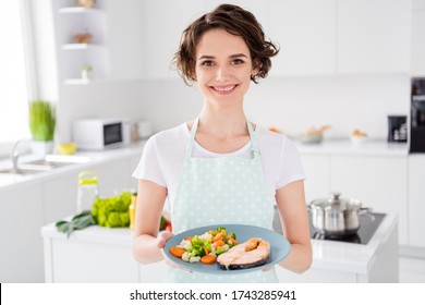 Photo of attractive housewife lady chef showing grilled salmon trout fillet steak roasted garnish cook dinner one person portion offer to try wear apron modern kitchen indoors