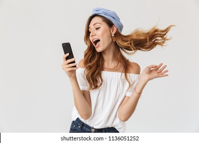 Photo of attractive joyous woman 20s smiling and holding mobile phone isolated over white background