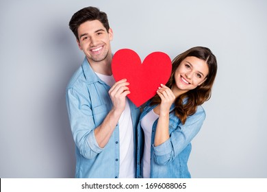 Photo attractive lady handsome funny guy demonstrating per paper heart figure big postcard symbolizing love emotions wear casual denim shirts outfit isolated grey color background