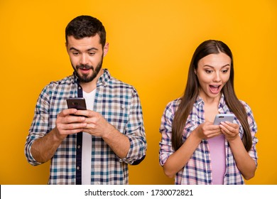 Photo attractive lady handsome guy couple look speechless telephone screen open mouth good news addicted popular bloggers wear casual plaid shirts outfit isolated yellow color background