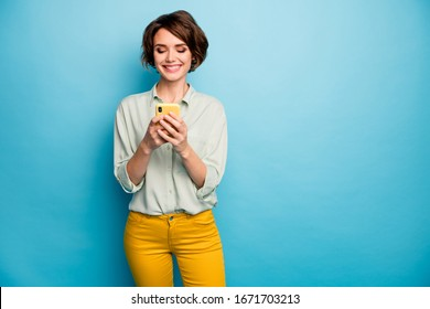 Photo of attractive lady holding telephone hands reading new blog post positive comments popular blogger wear casual green shirt yellow trousers isolated blue color background