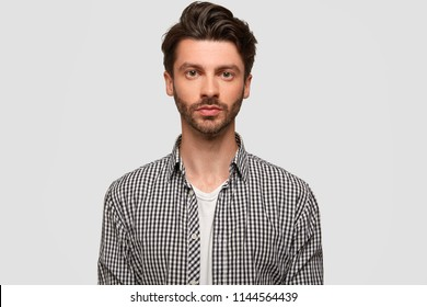 Photo of attractive man with stylish hairdo, has stubble, looks directly at camera seriously, wears checkered shirt, isolated over white studio wall. Confident male manager works, models indoor