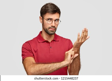 Photo of attractive man wears round spectacles, keeps hand on wrist, checks pulse or heart rate, cares of his health, has heart palpitation, models against white background. Pulse assesment concept