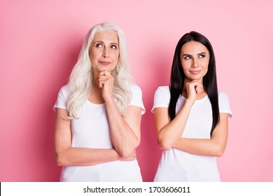 Photo of attractive old mother with young pretty daughter two ladies look side empty space think of holiday surprise wear casual white t-shirts isolated pastel pink color background