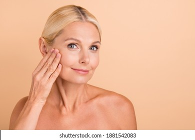 Photo of attractive perfect beauty aged lady nude shoulders touch cheek apply anti age cream isolated beige color background