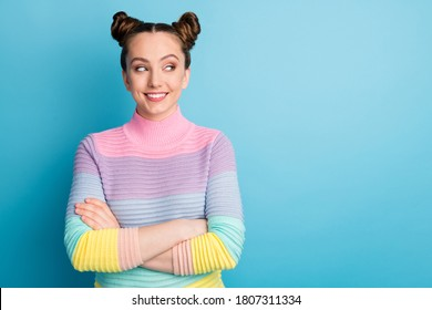 Photo of attractive teen lady two funny buns good mood toothy smile nice youngster arms crossed look side empty space interested wear casual striped sweater isolated blue color background