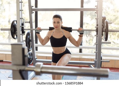 Photo of attractive woman doing lunge exercise with barbell load on back, being strong, shapely, endurance, lifts glutes, develops strength, gains muscle mass, uses workout gear, reaches her goals.