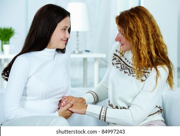 Photo of attractive woman and her teenage daughter looking at each other