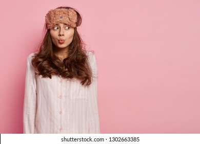 Photo of attractive woman makes grimace, pouts lips, wears eyemask and pyjamas, concentrated aside, feels puzzled after awakening early, isolated over pink wall with empty space for your slogan