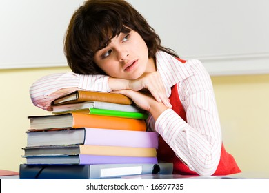 Photo of attractive woman putting her head onto stack of books and looking aside