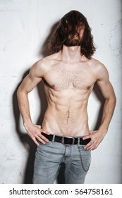 Photo of attractive young bearded hipster man posing isolated over wall background.