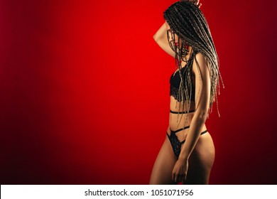 Photo of attractive young beauty woman with a gorgeous figure  in lingerie on a red background.