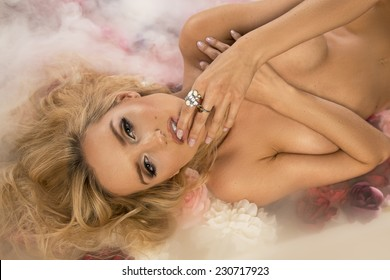 Photo of attractive young blonde beauty posing, lying on flowers.