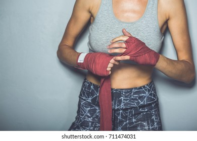 Photo of attractive young boxer lady posing over grey background, focus on hands