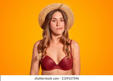 Photo of attractive young female cant stand stuff hot weather conditions during summer, blows air, feels sultry, dressed in swimwear and summer hat, isolated over orange background. Midday sun.