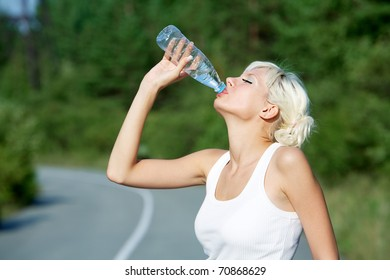 Photo of attractive young girl drinking water on the road during summer hot day