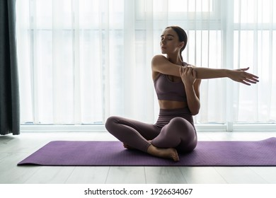 Photo of attractive young lady warming up her hands at home. Young woman training and stretching arm at home. Woman stretching arms before workout at home. Female doing warm up exercise.