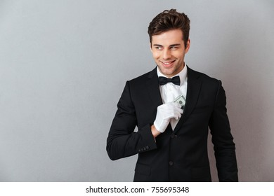 Photo of attractive young waiter standing isolated over grey wall background. Looking aside while holding money.