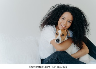 Photo of attractive young woman with Afro hircut, embraces with love dog, takes care of pet, smiles gently, wears casual clothing, isolated over white background, sit on bed, copy space for your promo