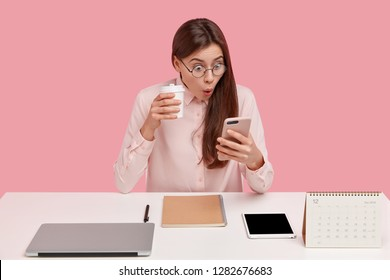 Photo of attractive young woman reads shocking news on mobile phone, watches video in social networks, drinks coffee from disposable cup, being office perfectionist, uses electronic gadgets.