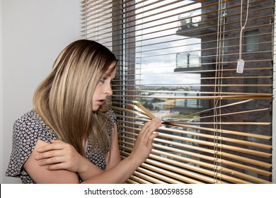 Photo of an attractive young woman wearing a summer dress with flowers on it looking scared and unhappy while looking at out of the window with metal blinds in an apartment in the UK