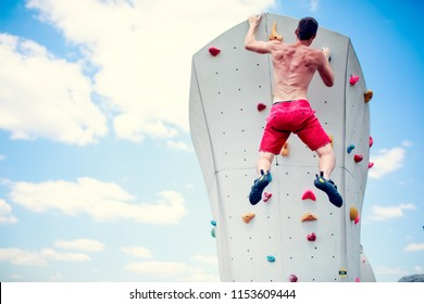 Photo from back of athlete man in red shorts practicing on wall for climbing against blue sky with clouds