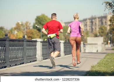 Photo from back of athletic pair running along promenade