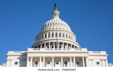 Photo of the back of The Capitol Building in Washington, DC with a bright blue sky.