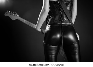 Photo of the back of a female guitar player standing and playing in front of a spotlight. Slight film grain added.