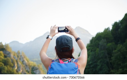 Photo from back of girl with backpack with smartphone