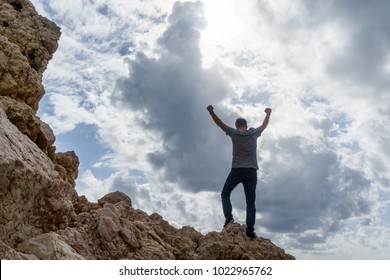 Photo from back of man with hands up on mountain