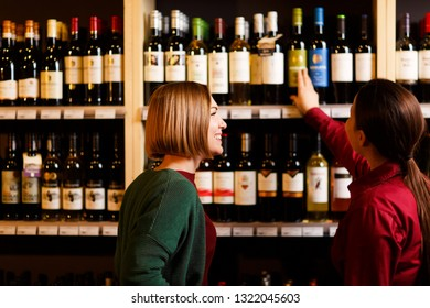 Photo from back of two young women at wine store