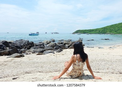 Photo from the back of women asia sitting on the beach at sae thailand.