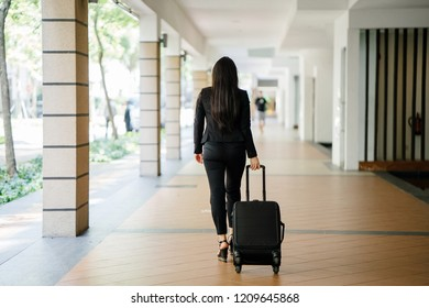 Photo of the back of a young, attractive and beautiful Chinese Asian woman in a suit pulling a luggage on wheels during the day as she walks away from the viewer.