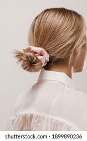 Photo from back of young blonde with white blouse and pastel pink scrunchie, trendy hairstyle, posing isolated over light background