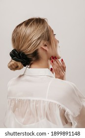 Photo from back of young lady with blonde hair, white silk shirt and red manicure, touching neck tender and looking away. Girl posing isolated over light background