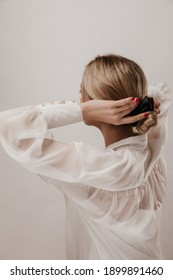 Photo from back of young tender girl with blonde hair, black scrunchie and white silk shirt, adjusting hairstyle and posing isolated over light background
