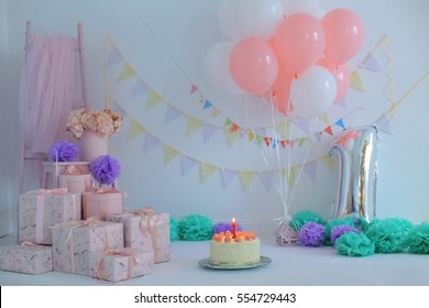 Photo background for celebrating  first birthday with sweet cake on a light party background with pink gift boxes, flowers, colorful decorations, flag garland and balloons. Kids party organization