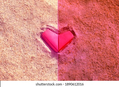 Photo background pink paper heart on the sand of the beach. Example of a heart for Valentine's Day