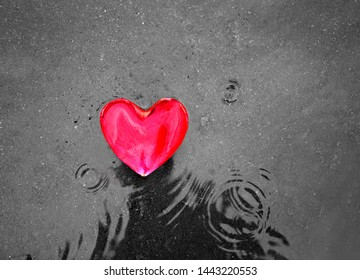 Photo background of red rose heart petal on the pavement with raindrops. Festive background to the Day of lovers.