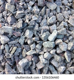 Photo background stones rubble and gravel. The texture of the granite stones is gray and white.