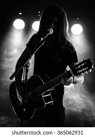 Photo of a backlit young man with long hair in silhouette playing an acoustic guitar on stage.