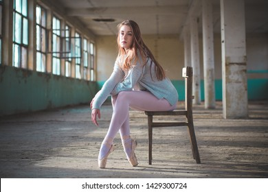 Photo of ballerina while shes sitting on the chair in an old building. Young, elegant, graceful woman ballet dancer
