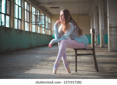 Photo of ballerina while she's sitting on the chair in an old building. Young, elegant, graceful woman ballet dancer