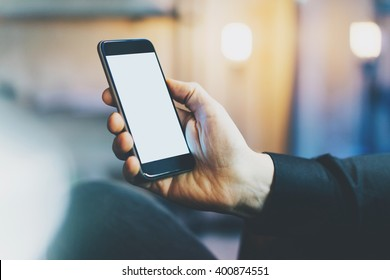Photo banker relaxing in modern loft office.Man sitting chair night.Using contemporary smartphone,blurred background.Blank screen ready for your business information.Horizontal,film effect.