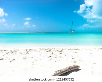 Photo of Beach MalTiempo in Cayo Largo, Isla de la Juventud, Cuba, in celeste blue showing a wood trunk covered by white sand, a ship resting on the sea and a sand strip on the sea with a beach chair