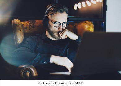 Photo bearded businessman wearing glasses relaxing modern loft office.Man sitting in vintage chair,listening music laptop night.Using contemporary notebook, blurred background.Horizontal,film effect.