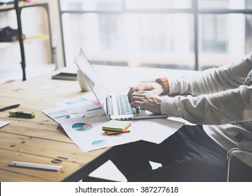 Photo bearded businessman working with new project modern loft. Generic design notebook on wood table.  Analyze plans, papers, hands texting keyboard. Blurred background, film effect