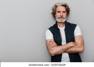 Photo of a bearded concentrated handsome senior man with grey hair isolated over grey wall background.