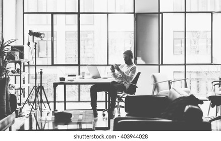 Photo bearded creative manager working with new project open space loft studio. Looking modern smartphone. Contemporary laptop on wood table. Black and white.Blurred background, film effect,horizontal
